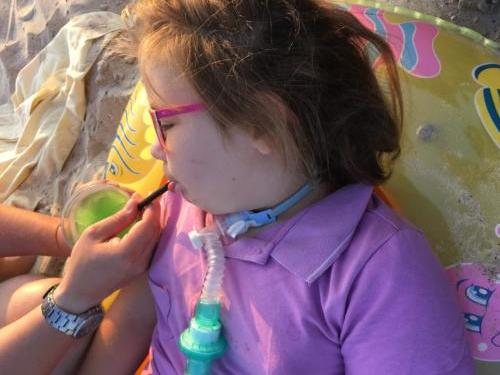 Marysia na plaży w Ustce pije ze słomki